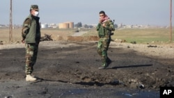 In this undated photo made available March 14, 2015, by the Kurdistan Region Security Council, Kurdish soldiers survey what Kurds now say was the site of a chemical-weapons attack between Mosul, Iraq, and the Syrian border in northern Iraq.