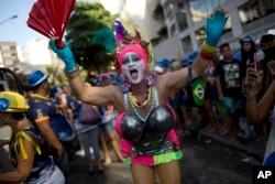 "A reveler in costume attends the Banda de Ipanema carnival ""bloco"" parade in Rio de Janeiro, Brazil, Feb. 11, 2017. Merrymakers take to the streets in hundreds of open-air ""bloco"" parties ahead of Rio's over-the-top Carnival."