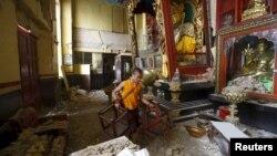 Seorang pendeta Budha membawa kursi keluar dari kuilnya yang rusak akibat gempa di Kathmandu, Nepal (28/4).