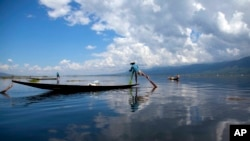 An ethnic Inntha fishermen on boats use their fishing net in Inlay lake, Nyaung Shwe township, southern Shan State, Myanmar, Wednesday, Oct. 1, 2014.