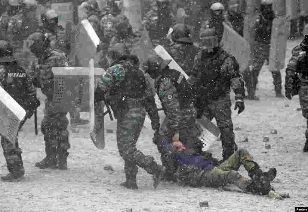 Riot police hold a man during clashes with pro-European protesters in Kyiv, Jan. 22, 2014.