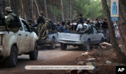 FILE - This July 9, 2017, photo — released by Ibaa news agency, the communications arm of the al Qaeda-linked Levant Liberation Committee, that is consistent with independent AP reporting — shows al-Qaida-linked fighters gathering ahead of raids in the northwestern Syrian city of Idlib in search for members of the Islamic State group.