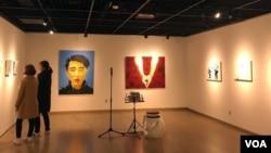 탈북자 출신 래퍼 강춘혁 씨의 그림 전시회 '혁명'에서 관람객들이 작품을 감상하고 있다.