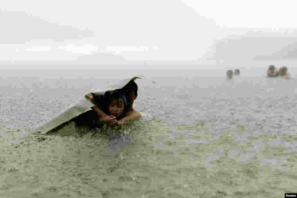 A man and a young girl covers themselves from the rain with a banana leaf in the sea on the outskirts of Colon City, Panama, Oct. 17, 2015.