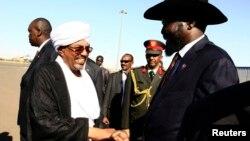 Sudanese President Omar Hassan al-Bashir shakes hands with South Sudan's President Salva Kiir, right, at Khartoum Airport, Nov. 4, 2014.