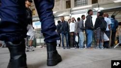 Des migrants font la queue pour être enregistrés par des bénévoles de Progetto Arca avant d'être conduits à un centre à Milan, en Italie, le dimanche 14 juin 2015.