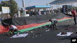 Những người Afghanistan thu lượm những gì còn xót lại sau một đánh bom chết người xảy ra tại một cuộc biểu tình của sắc dân Hazaras, ở Kabul, Afghanistan, thứ bảy ngày 23 tháng 7 năm 2016.