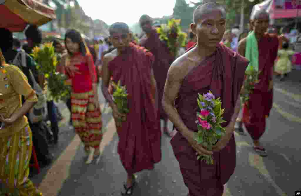 Buddhist monks and devotees carry flowers to offer at Shwedagon pagoda in Rangoon, Burma, April 17, 2014.