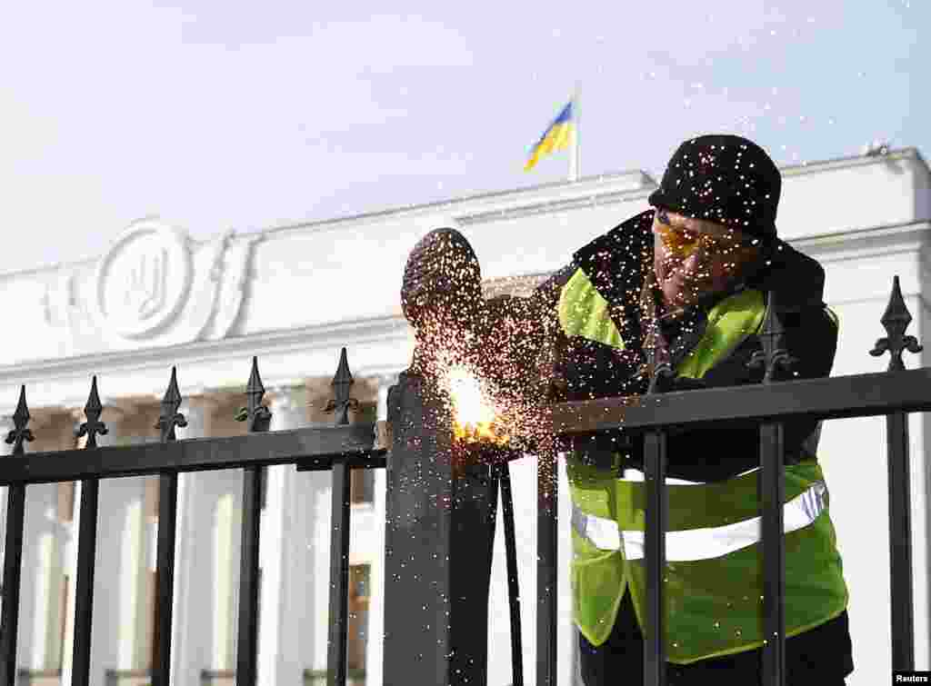 A member of a self-defense unit saws a fence enclosing the parliament building in Kyiv, Feb. 26, 2014.