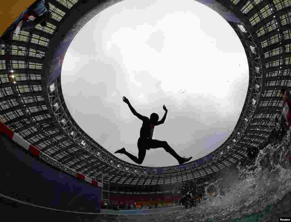 Paul Kipsiele Koech of Kenya jumps a water obstacle in the men's 3000 metres steeplechase heat during the IAAF World Athletics Championships at the Luzhniki Stadium in Moscow, Russia.