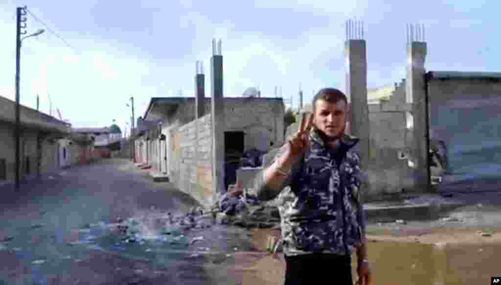 A Free Syrian Army soldier flashes the victory sign as damages caused by warplanes and rocket launchers is seen at background in Hama, Syria, January 28, 2013. Image taken from video.