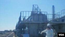 Seorang petugas di Jepang menunjukkan retakan yang ditemukan dekat reaktor No. 2 PLTN Fukushima, Minggu (3/4).