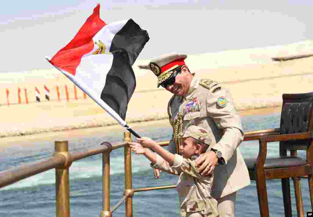 In this picture provided by the office of the Egyptian Presidency, President el-Sissi smiles at a boy as he waves the national flag from a monarchy-era yacht that sailed to the venue of a ceremony for extension of the Suez Canal, 6 Aug. 2015.