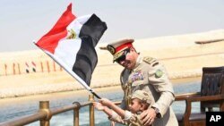 In this picture provided by the office of the Egyptian Presidency, President el-Sissi smiles at a boy dressed in a tiny military uniform as he waves the national flag from a monarchy-era yacht that sailed to the venue of a ceremony for extension of the Su