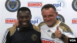 Freddy Adu (kiri) yang baru dikontrak klub MLS Philadelphia Union tersenyum di samping pelatihnya Peter Nowak dalam konferensi pers di Chester, Pennsylvania, Jumat (12/8).