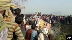 In this image from video, people gather at the site where a truck loaded with sand collided with a school bus in the northern Indian state of Uttar Pradesh, Jan. 19, 2017.