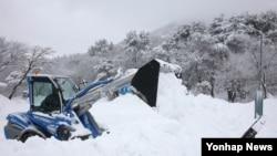 한파와 폭설이 몰아친 19일 제주 한라산국립공원 어리목 코스에서 공원 관계자가 중장비를 이용해 제설하고 있다.