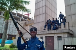 Congolese policemen sit on a monument at the Central Station, in Gombe, Kinshasa, Democratic Republic of Congo, Dec. 19, 2016.