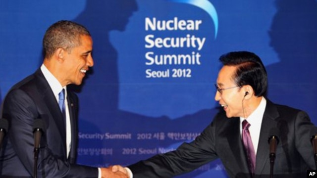 U.S. President Barack Obama, left, shakes hands with his South Korean counterpart Lee Myung-bak during a joint press conference following their meeting at the presidential Blue House in Seoul, South Korea, Sunday, March 25, 2012.