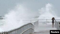 Una mujer camina por un muelle batido por las fuertes olas causadas por el huracán Sandy a su paso mar afuera frente a Ponce Inlet, en la costa este de Florida.