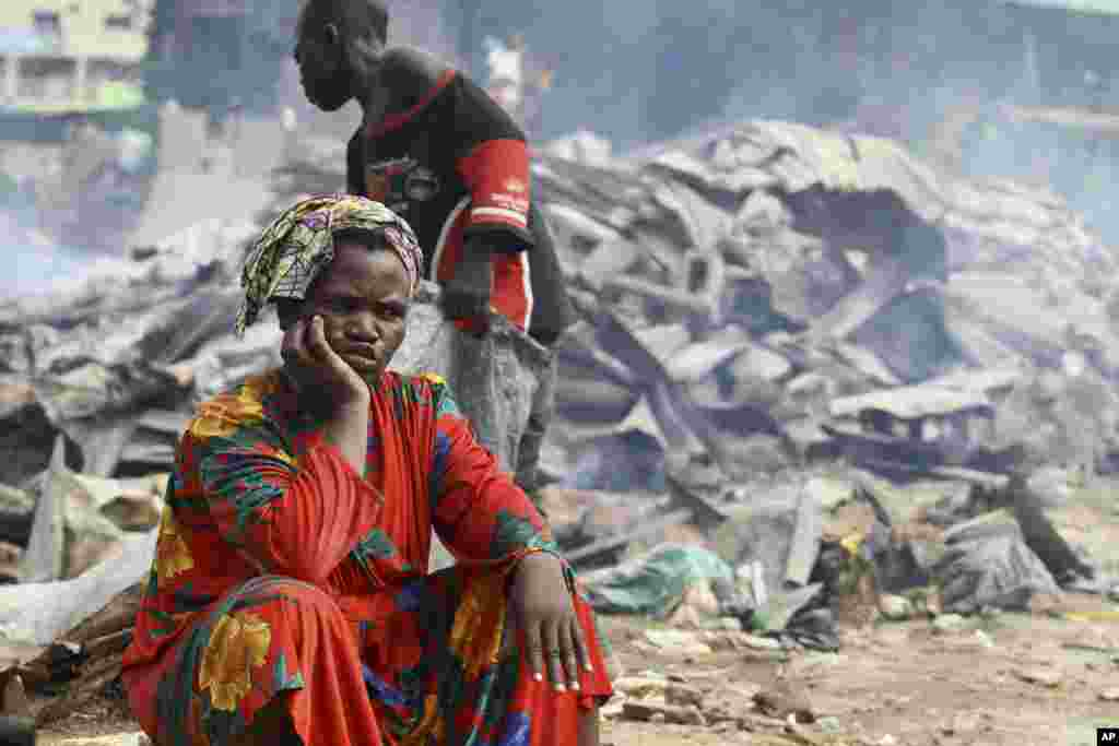 A woman sits near burnt roofing sheets after the Abuja enviromental task force pulled down illegal structures in Utako district in Abuja July 7, 2011. REUTERS/Afolabi Sotunde(NIGERIA - Tags: SOCIETY)
