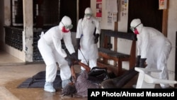 Petugas kesehatan berpakaian pelindung memindahkan seseorang yang dicurigai meninggal karena Ebola di Monrovia, Liberia (16/9). (AP/Abbas Dulleh)