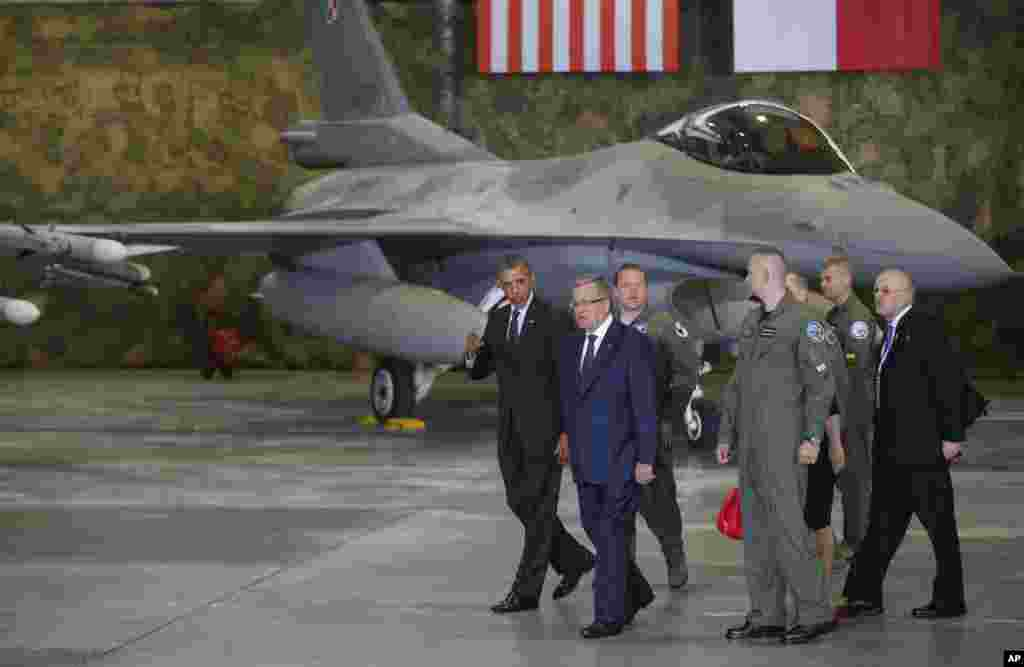 U.S. President Barack Obama and Poland's President Bronislaw Komorowski walk to make statements after meeting U.S. and Polish troops at an event featuring F-16 fighter jets in Warsaw, June 3, 2014.