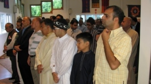 FILE - American Muslims offer Eid al-Fitr prayers in a community center in northern Virginia, Aug. 8, 2013. Muslims are relatively few in number in the U.S. but tend to live in swing states that can have an impact on election outcomes. (M. Elshinnawi/VOA)