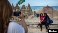 People pose for photos next to a sand sculpture of Pope Francis, Copacabana beach, Rio de Janeiro, July 16, 2013.