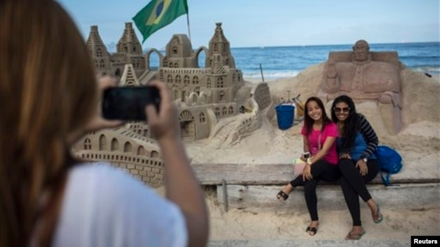 People pose for photos next to a sand sculpture of Pope Francis, Copacabana beach, Rio de Janeiro, July 16, 2013.