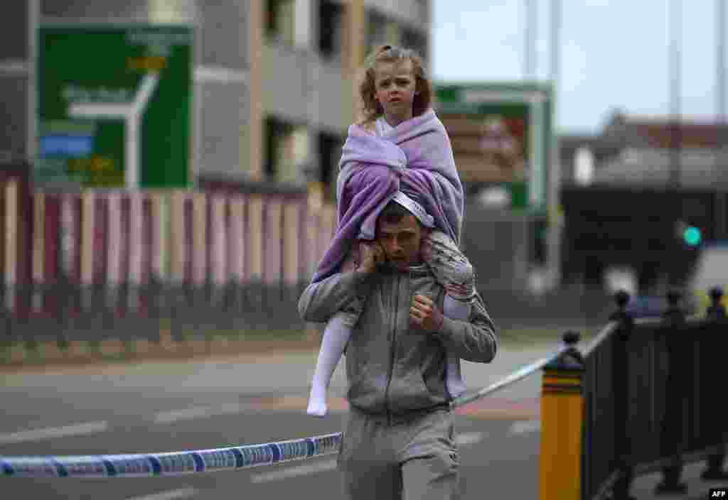 A man carries a young girl on his shoulders near Victoria station in Manchester, northwest England. Twenty two people have been killed and dozens injured after a suspected suicide bomber targeted fans leaving a concert of U.S. singer Ariana Grande in Manchester.
