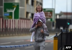 A man carries a young girl on his shoulders near Victoria station in Manchester, northwest England, May 23, 2017.