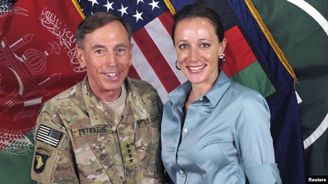 FILE - General David Petraeus, former CIA chief and commander of the International Security Assistance Force/U.S. Forces in Afghanistan, shakes hands with author Paula Broadwell in this handout photo from ISAF, originally posted July 13, 2011.