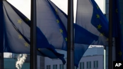 Asap mengepul dari cerobong asap di belakang bendera UE yang berkibar di luar markas UE di Brussel, Kamis, 24 Desember 2020.
