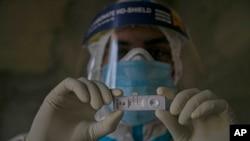 Arhiva - Zdravstveni radnik drži test na koronavirus.