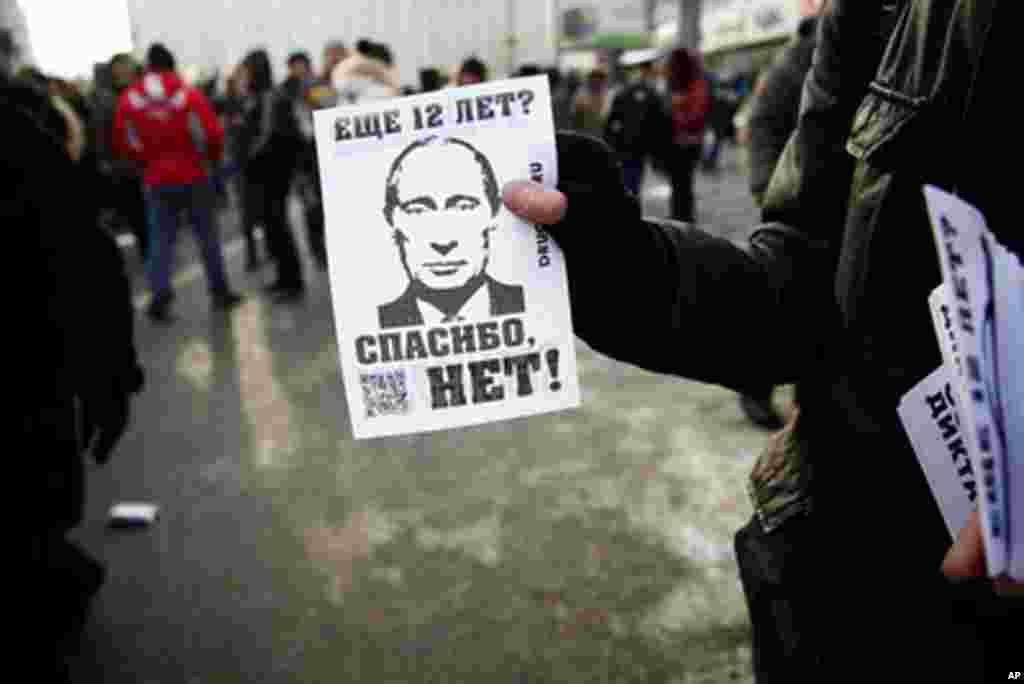 """An activist hands out flyers that say, """"12 more years? NO THANKS."""" February 4, 2012. (VOA - Y. Weeks)"""