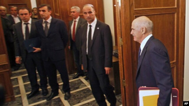 Aides and security officers watch as Greek Prime Minister George Papandreou arrives at an urgent cabinet meeting in the Greek parliament in Athens, Greece, November 3, 2011.