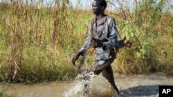 A rebel soldier patrols a flooded area near the town of Bentiu in Unity state. A report by the Geneva-based Small Arms Survey warns that both the rebels and government forces are planning new offensives in Unity state and elsewhere in South Sudan.