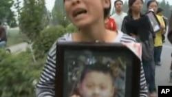 一位母亲手捧丧身汶川地震的儿子的照片(2008年资料照片)