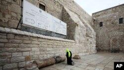 Seorang peziarah berdoa di luar Gereja Nativity di Betlehem, Tepi Barat, 5 Maret 2020. Pihak berwenang Palestina mengatakan gereja ini akan ditutup tanpa batas waktu untuk mengantisipasi merebaknya virus corona.