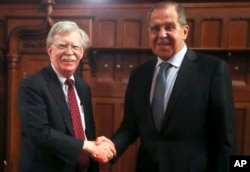 FILE - U.S. National Security Adviser John Bolton, left, and Russian Foreign Minister Sergey Lavrov shake hands prior to their talks in Moscow, Oct. 22, 2018.