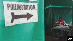 FILE - An election agent waits for people to cast their votes at a polling station on election day in Lusaka, Jan, 20, 2015.