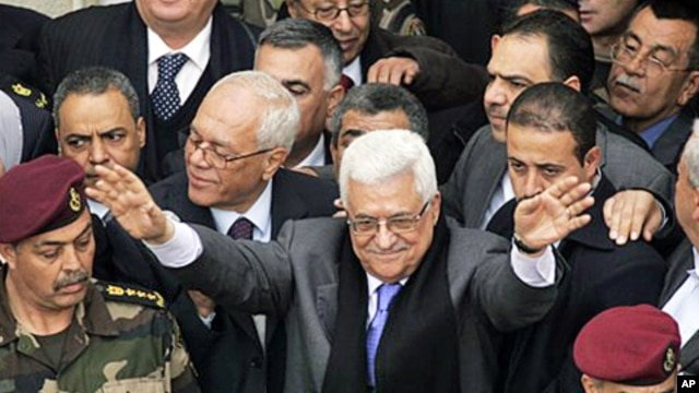 Palestinian President Mahmoud Abbas, center, gestures during a rally in the West Bank city of Ramallah, January 25, 2011