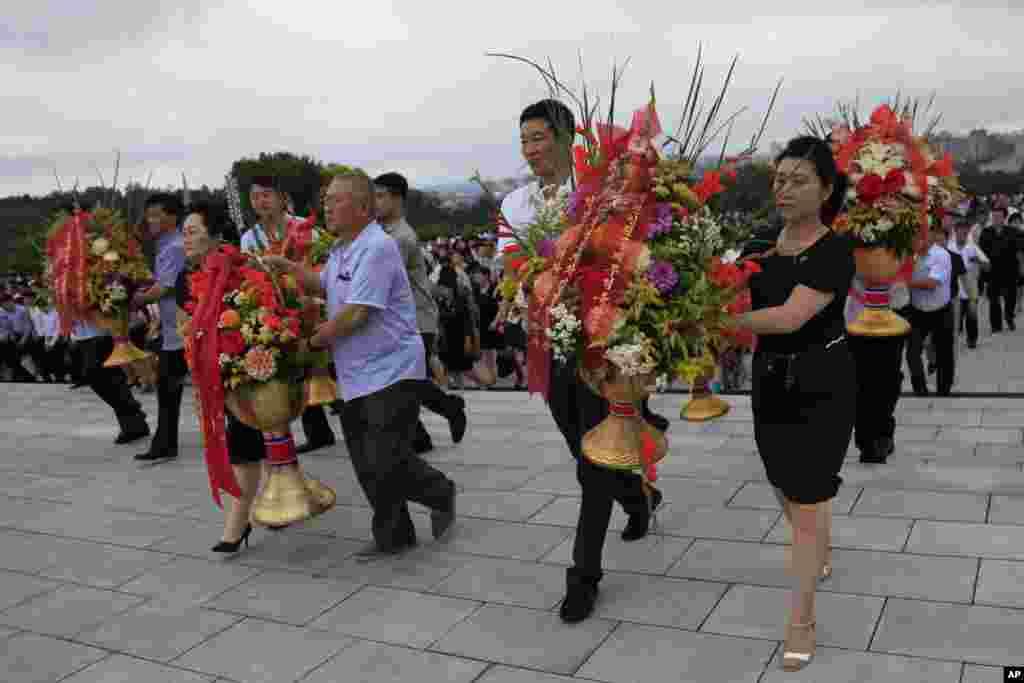 북한 김일성 주석 사망 23주기를 맞아 각 계층 근로자, 학생들이 꽃을 들고 김일성·김정일 동상을 향하고 있다.