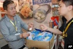廣州市民歐先生(右)試吃台灣花枝丸