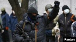 Uno de los asaltantes hace un gesto triunfal tras la ocupación de una estación de policía en el este de Ucrania.