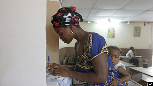 A woman with a baby on her back, votes at a polling station in Abidjan, Ivory Coast, December 11, 2011.