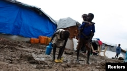 FILE - A boy carries a girl as they walk through the mud in an internally displaced persons (IDP) camp inside the U.N. base in Malakal, South Sudan, July 24, 2014.