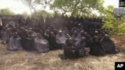 FILE - In this photo taken from video by Nigeria's Boko Haram terrorist network, Monday May 12, 2014 shows the alleged missing girls abducted from the northeastern town of Chibok. The new video purports to show dozens of abducted schoolgirls, covered in jihab and praying in Arabic.