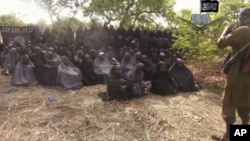 In this photo taken from video by Nigeria's Boko Haram terrorist network, Monday May 12, 2014 shows the alleged missing girls abducted from the northeastern town of Chibok. The new video purports to show dozens of abducted schoolgirls, covered in jihab